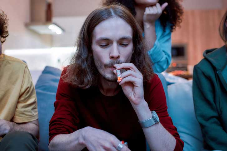 A young man smokes a joint