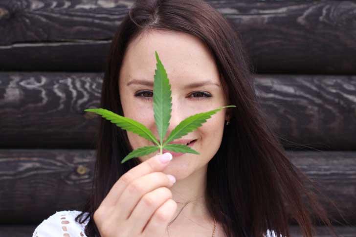 A woman holds a cannabis leaf